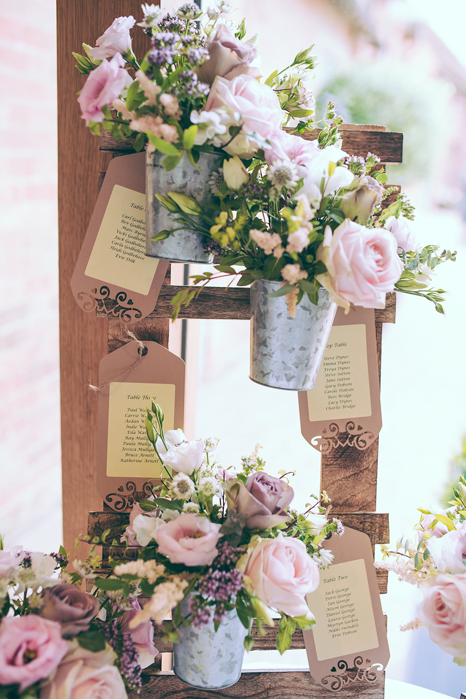 A couple adorned their wedding table plan at Bassmead Manor Barns with pink wedding flowers