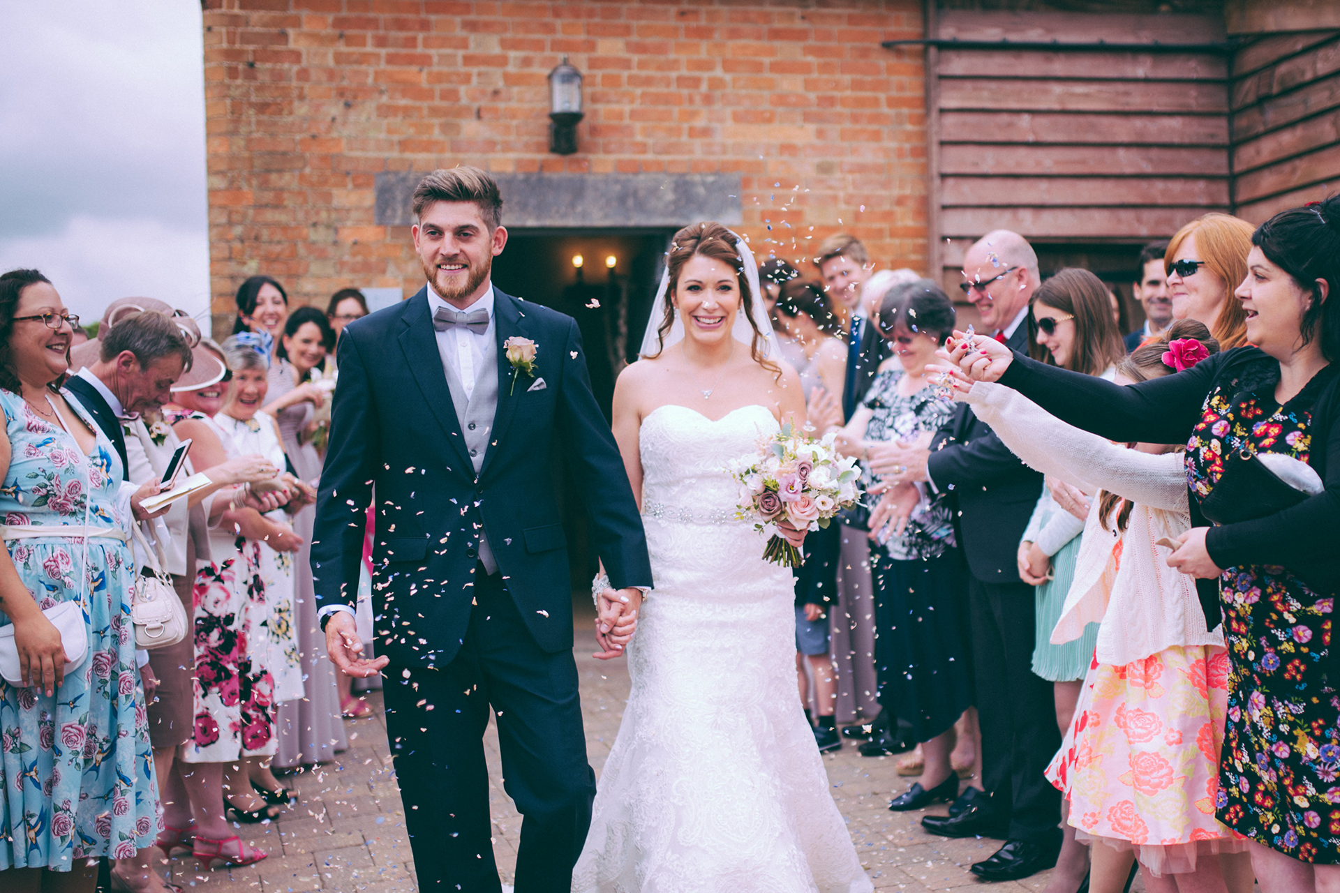 Newlyweds are showered with confetti after their wedding ceremony in the Rickety Barn at Bassmead Manor Barns