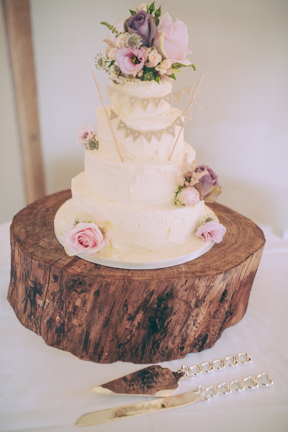 A three-tiered wedding cake sits on a rustic log slice for this summer wedding at Bassmead Manor Barns