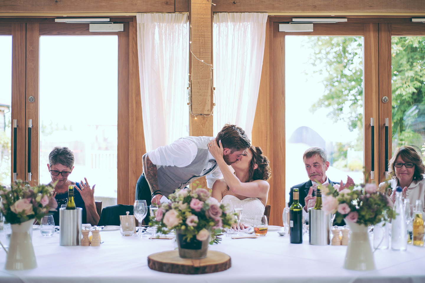 The newlyweds share a kiss during the wedding speeches in the Bridge Barn at Bassmead Manor Barns