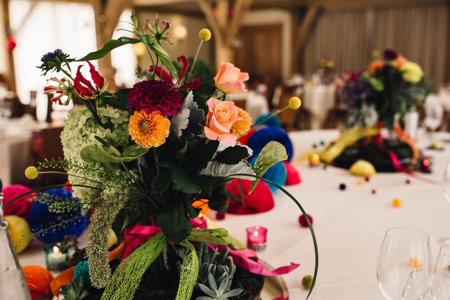 Vibrant floral table centrepieces were used to decorate the Moat Barn for the wedding breakfast