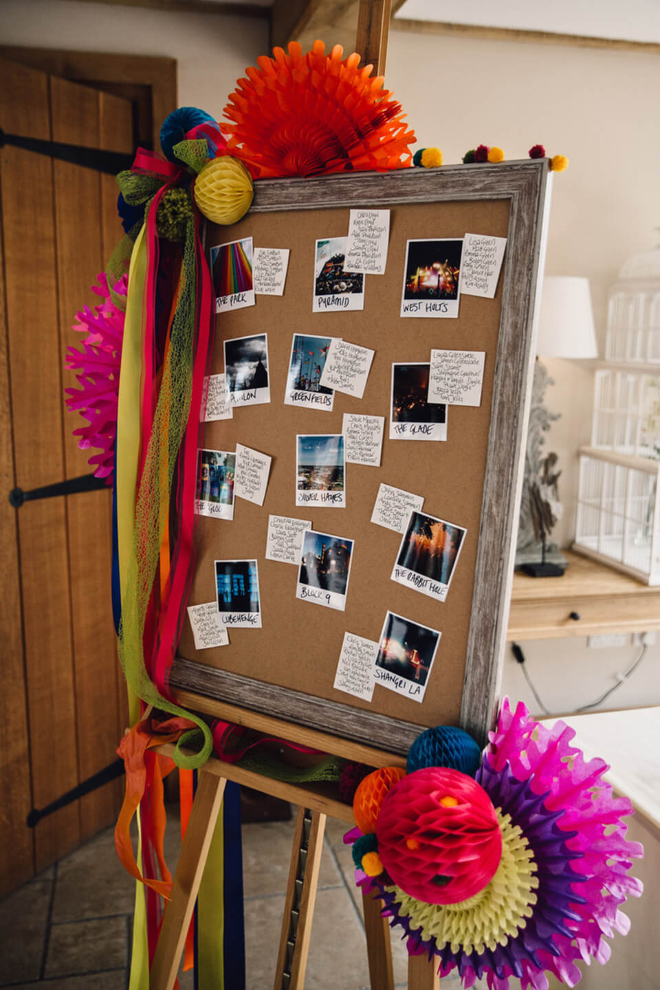 A wedding table plan is decorated with bright pom poms for this festival themed wedding