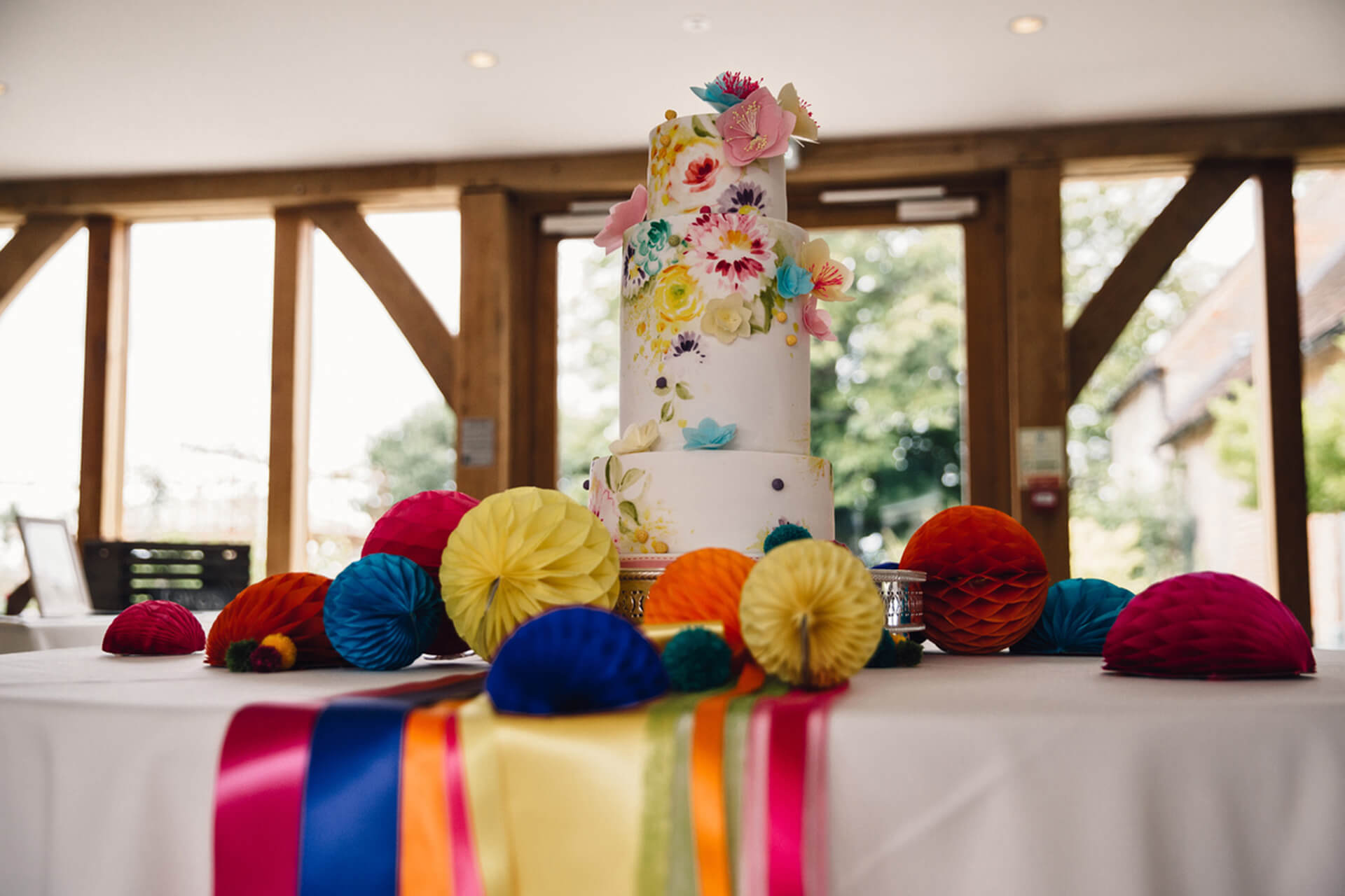 A white three tiered wedding cake is decorated with bright ribbons and wedding flowers