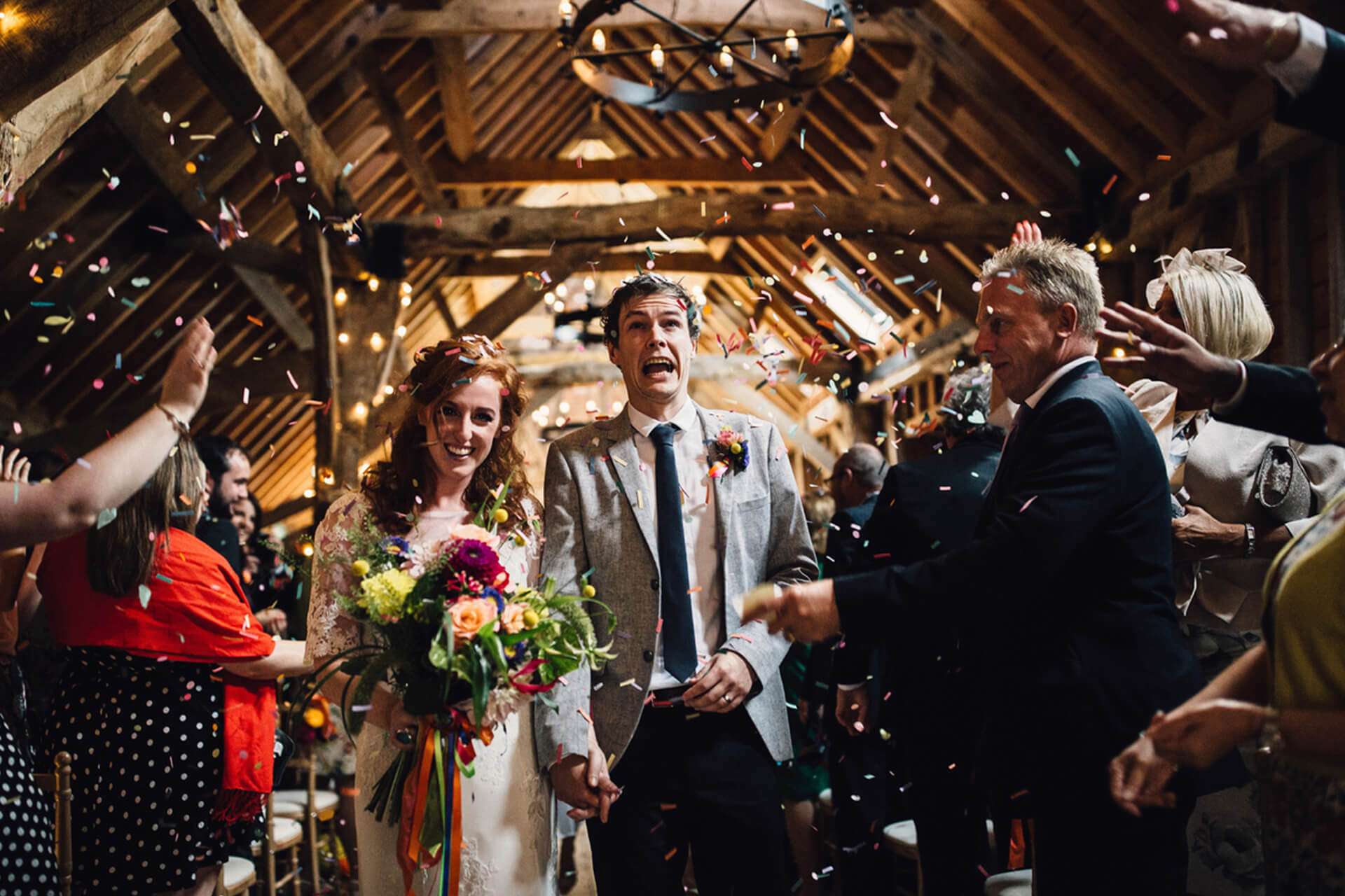 Guests throw wedding confetti over the newlyweds after their wedding ceremony