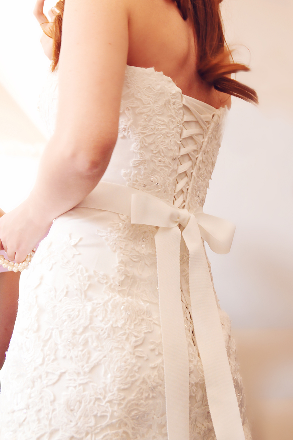 For her wedding at Bassmead Manor Barns the bride wore a white bridal gown with a corset back