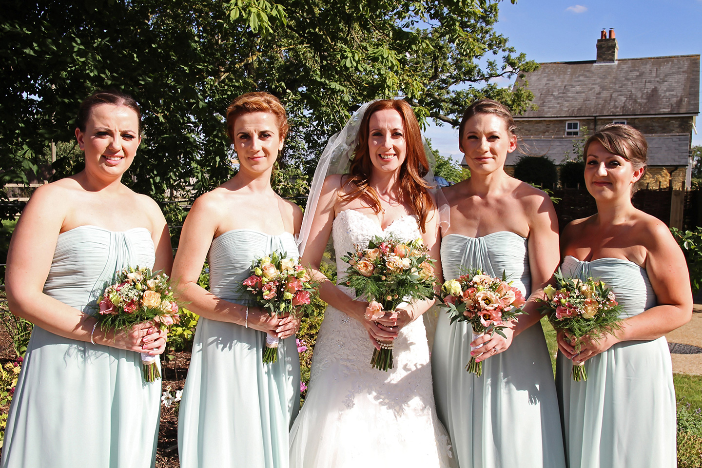 For this rustic wedding at Bassmead Manor Barns the bridesmaids wore pastel green strapless bridesmaids dresses