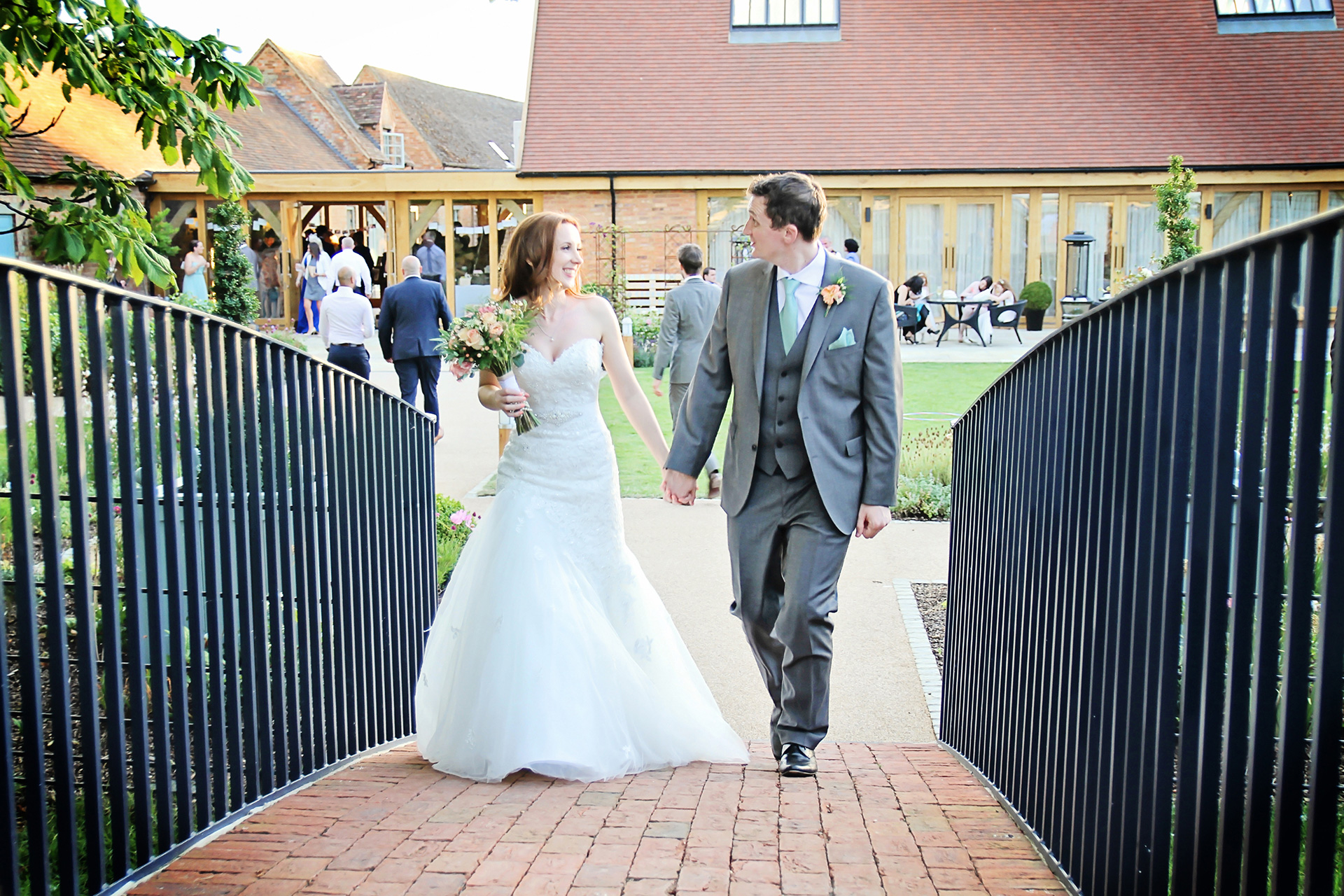 The bride and groom explore the gardens at Bassmead Manor Barns wedding venue in Cambridgeshire