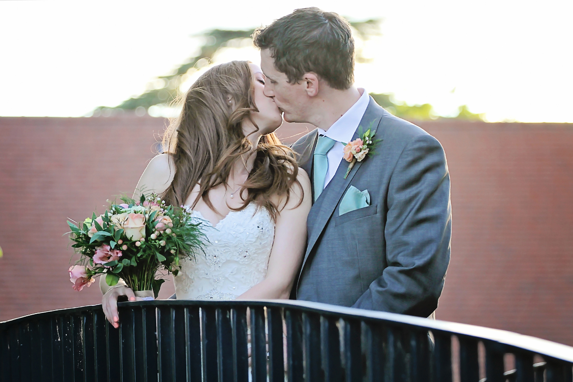 The bridge and groom share a kiss as the sun sets on their wedding day at Bassmead Manor Barns