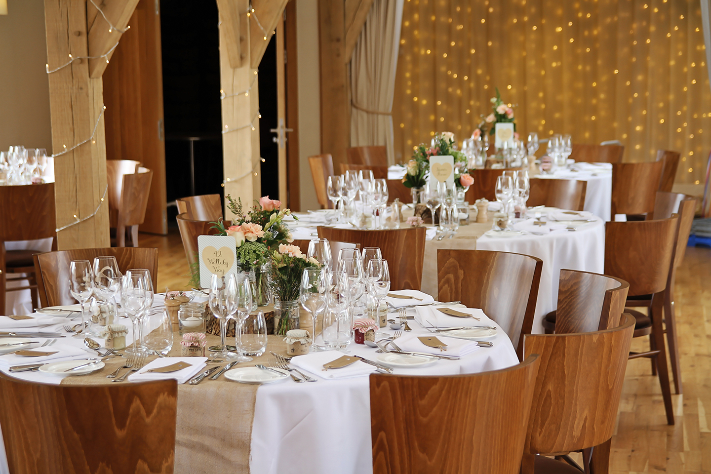 The Bridge Barn at Bassmead Manor Barns is set up for a rustic wedding breakfast