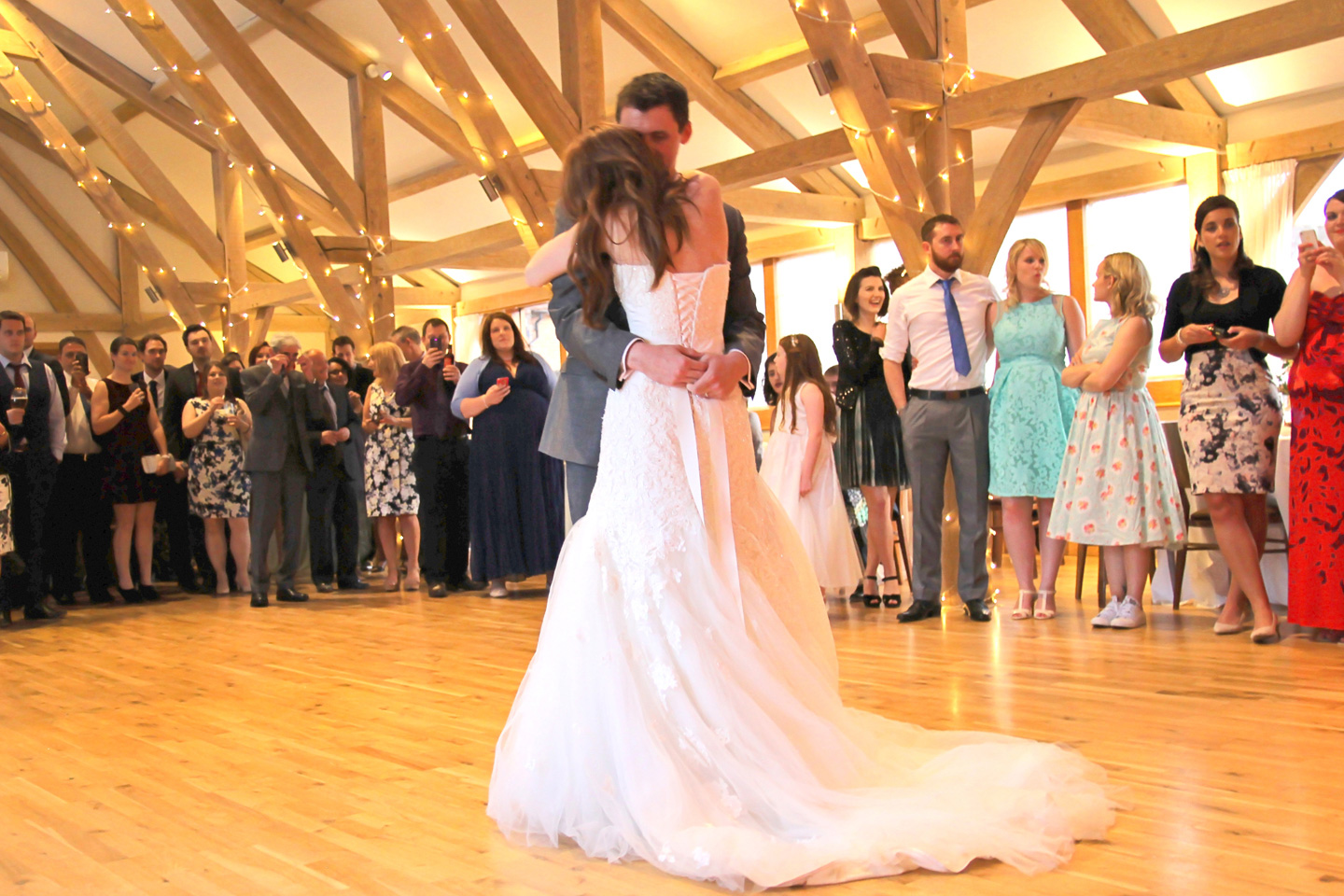The newlyweds perform their first dance in front of guests at Bassmead Manor Barns wedding venue in Cambridgeshire