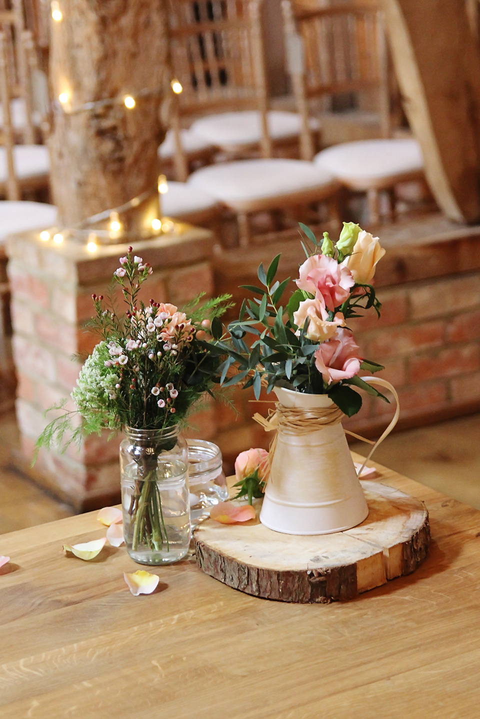 The couple decorated the Rickety Barn at Bassmead Manor Barns with rustic floral jars and log slices