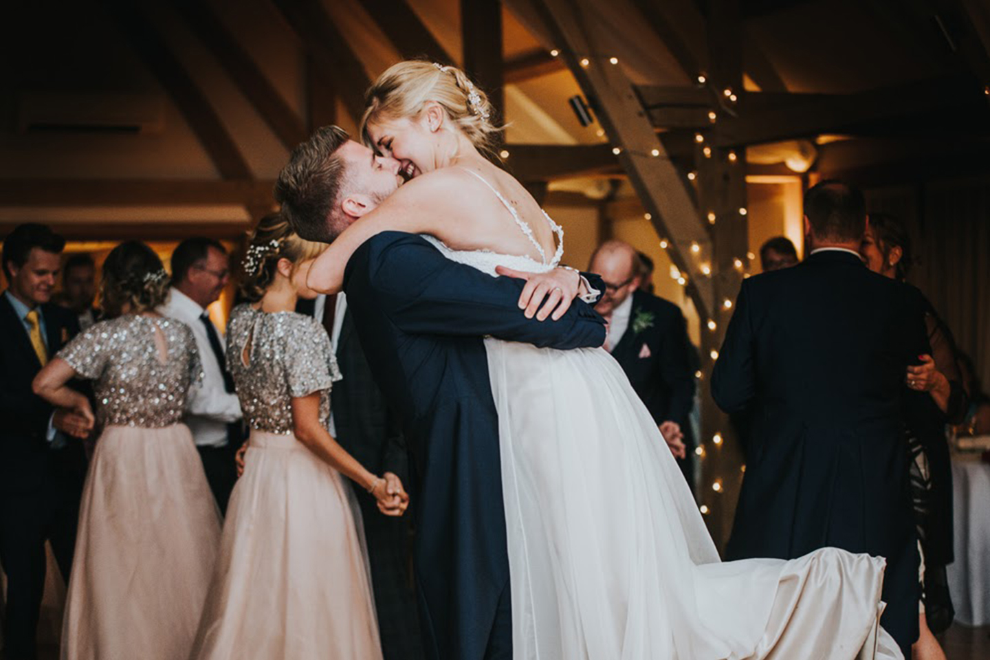 A bride and groom perform their first dance in front of guests at Bassmead Manor Barns