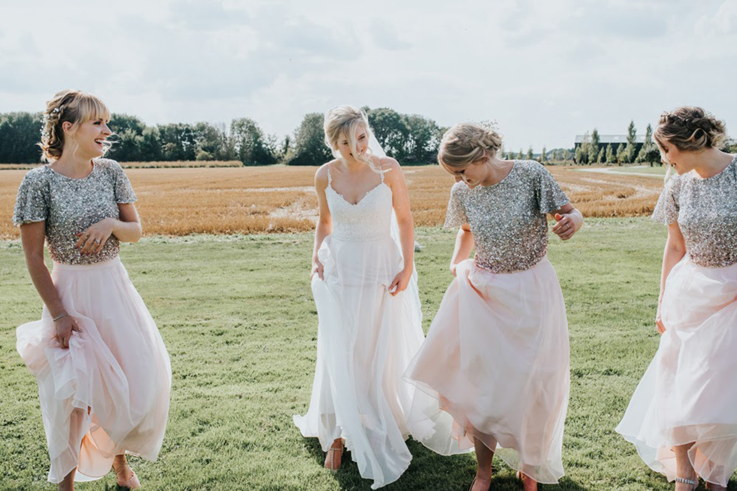 The bridesmaids wore sequin rose gold two piece dresses for this summer wedding at Bassmead Manor Barns