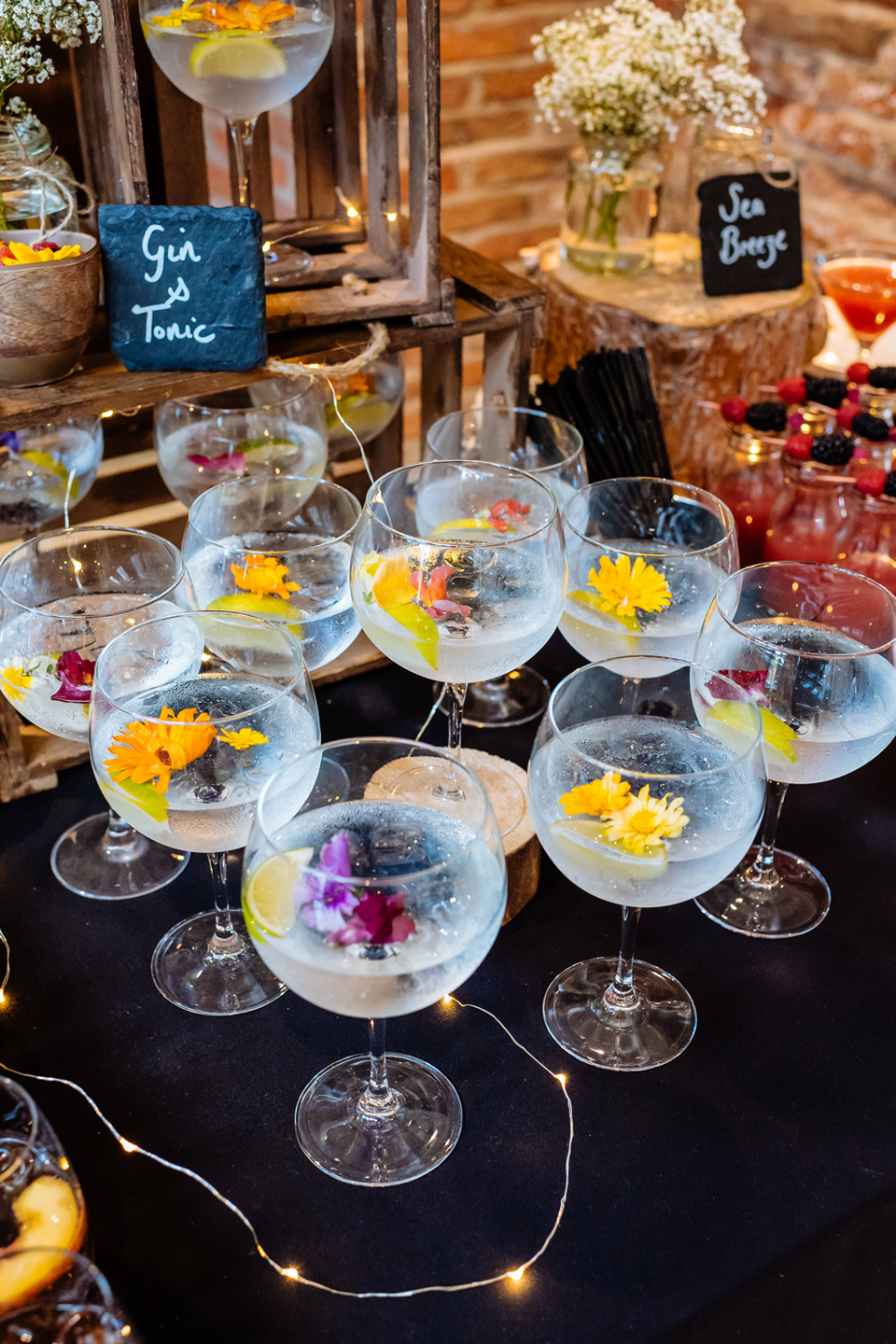A selection of gin and tonics are served with pretty flowers for a wedding reception at Bassmead Manor Barns