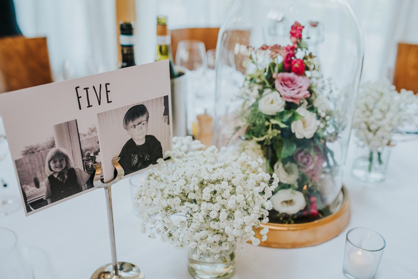 The couple used baby photographs as their table numbers during their wedding reception at Bassmead Manor Barns