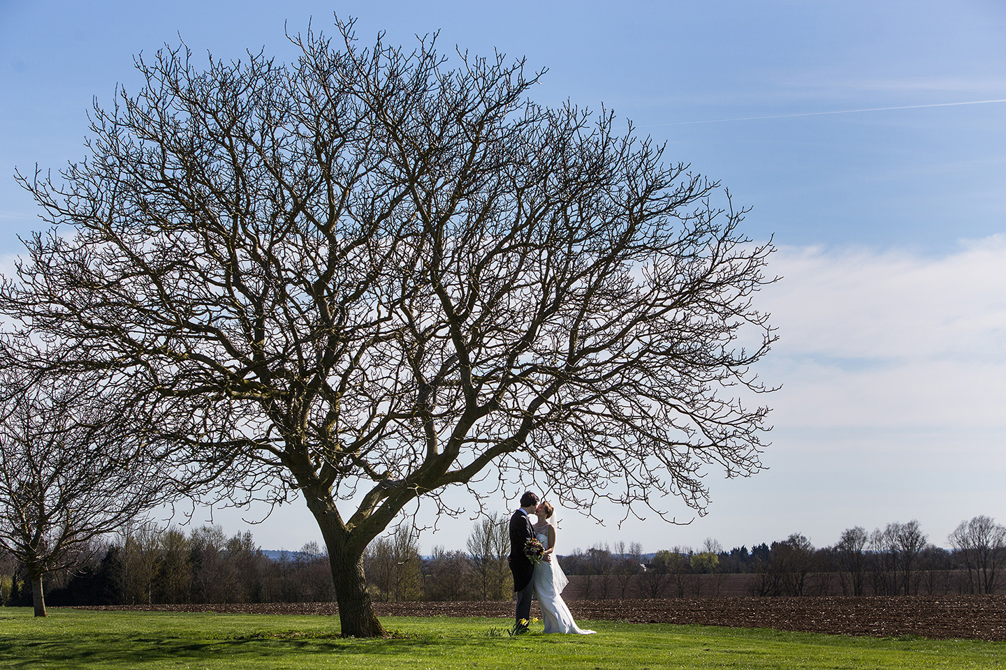 The bride and groom explore the Cambridgeshire countryside that surrounds Bassmead Manor Barns on their wedding day