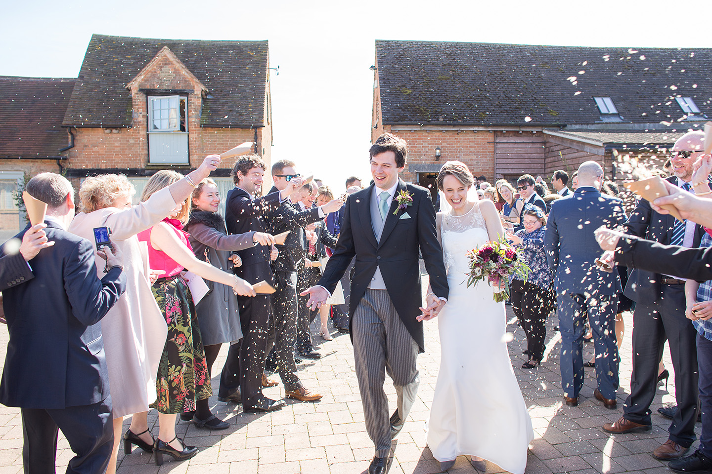 The bride and groom are showered in confetti after saying their vows in the Rickety Barn at Bassmead Manor Barns