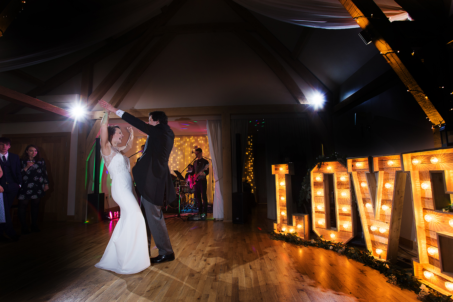 The bride and groom perform their first dance in front of giant light up love letters during their reception at Bassmead Manor Barns