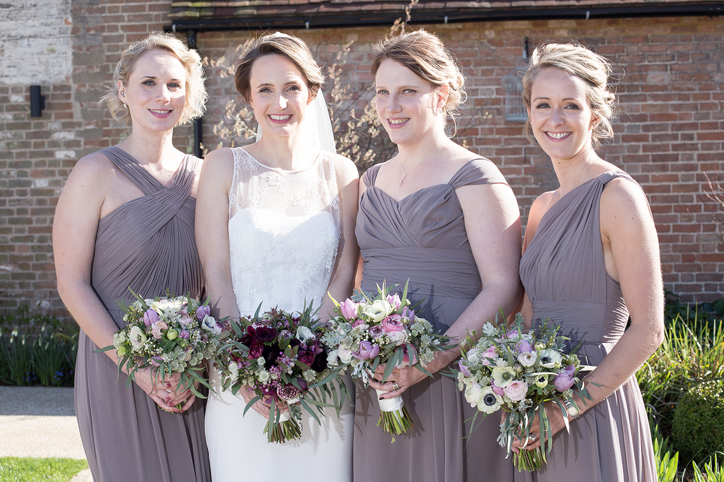 The bride stands with her bridesmaids who wear lilac dresses for this spring wedding at Bassmead Manor Barns