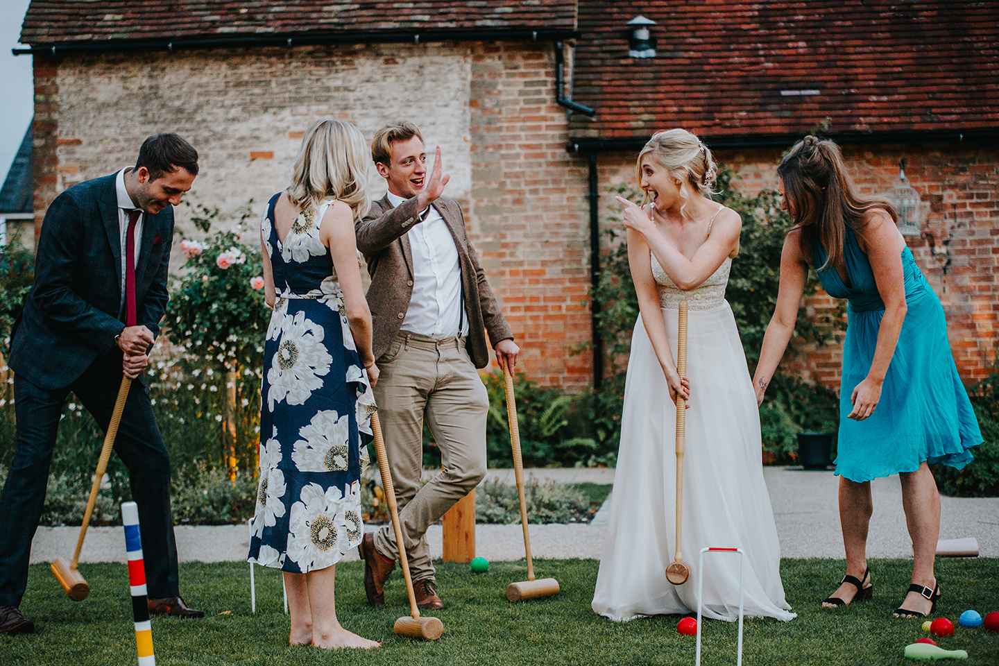 Guests play garden games during a spring wedding reception at Bassmead Manor Barns
