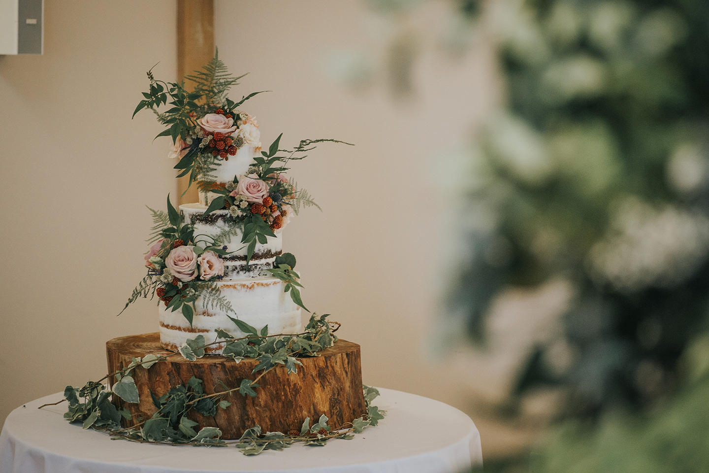 A naked wedding cake is decorated with flowers and berries for a spring wedding at Bassmead Manor Barns