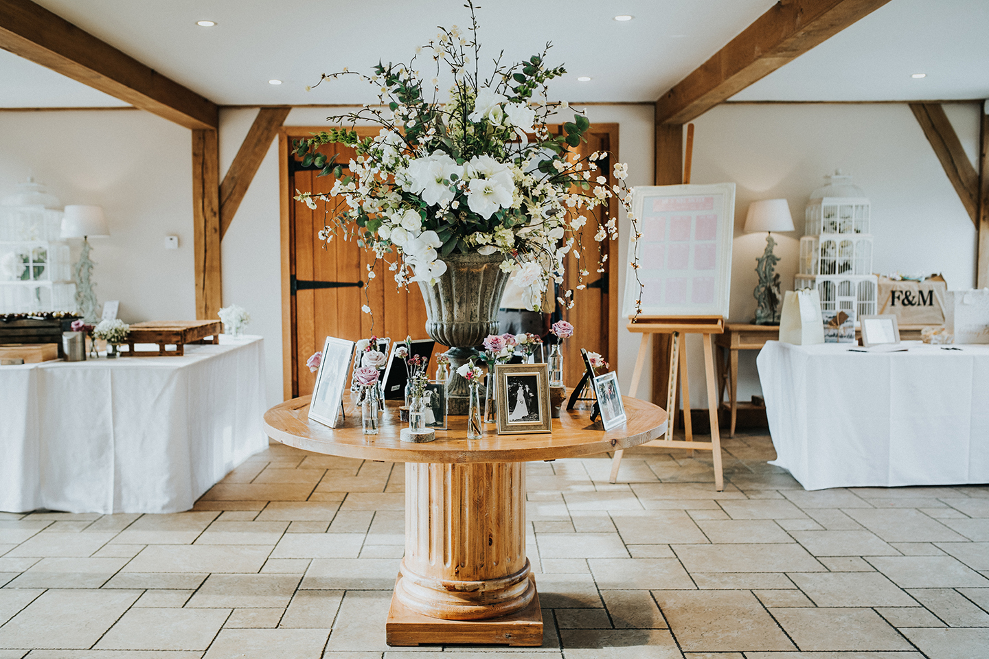 A table is decorated with white wedding flowers and personal touches for a spring wedding at Bassmead Manor Barns