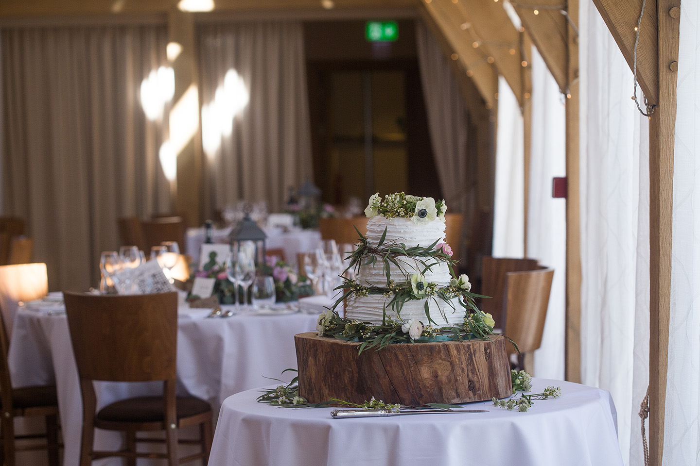 A rustic wedding cake is decorated with foliage and sits on a log slice for a spring wedding at Bassmead Manor Barns