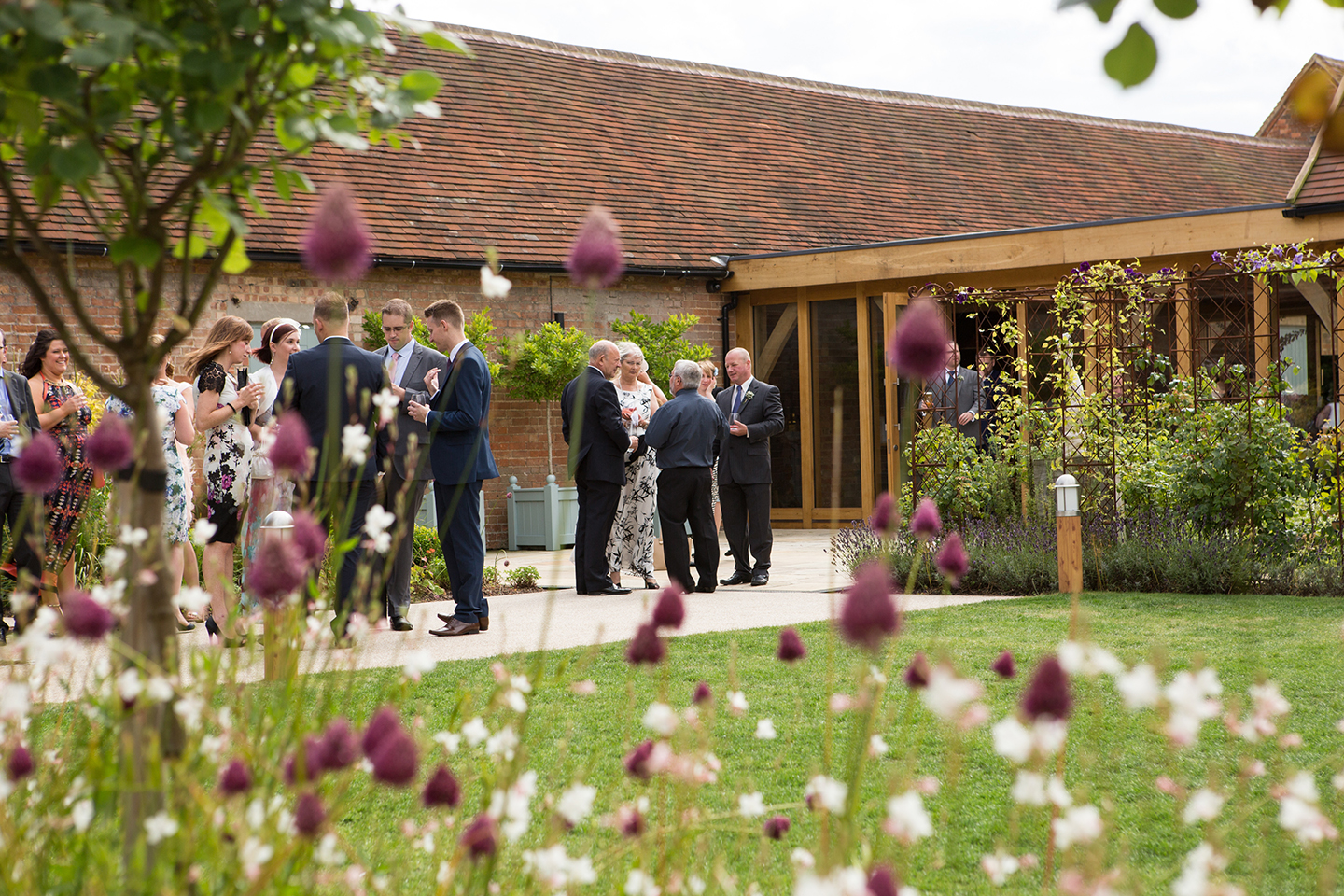 Guests enjoy a spring wedding drinks reception in the gardens at Bassmead Manor Barns