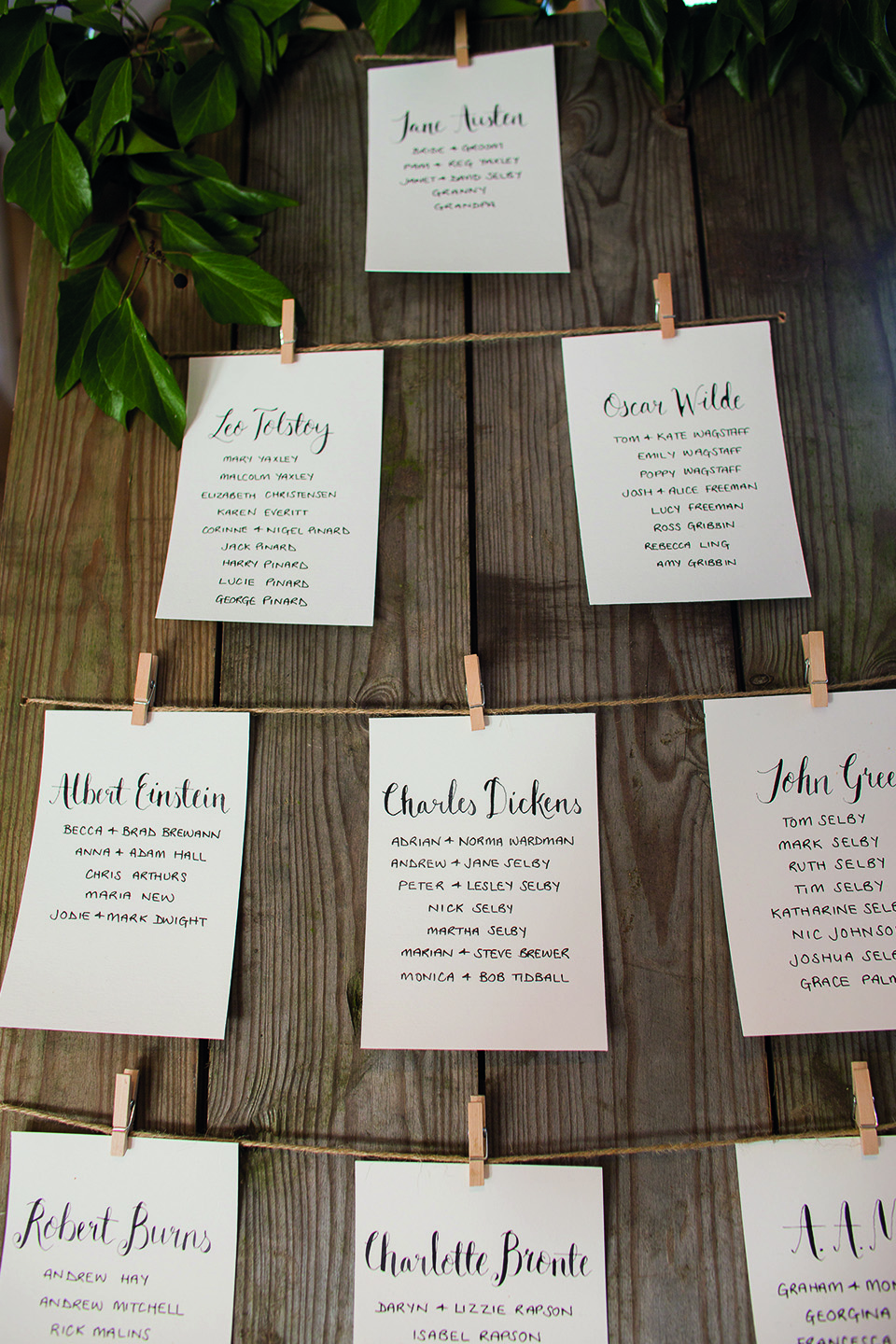 A hand written spring wedding table plan is pegged on to a wooden board for this country themed wedding at Bassmead Manor Barns