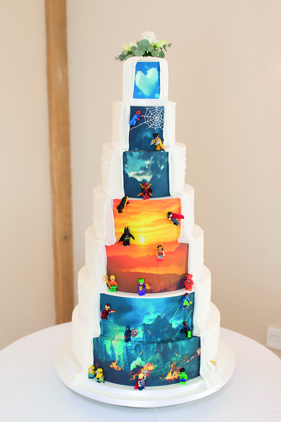 A traditional seven-tiered wedding cake has an alternative twist with a superhero unveiling at the back