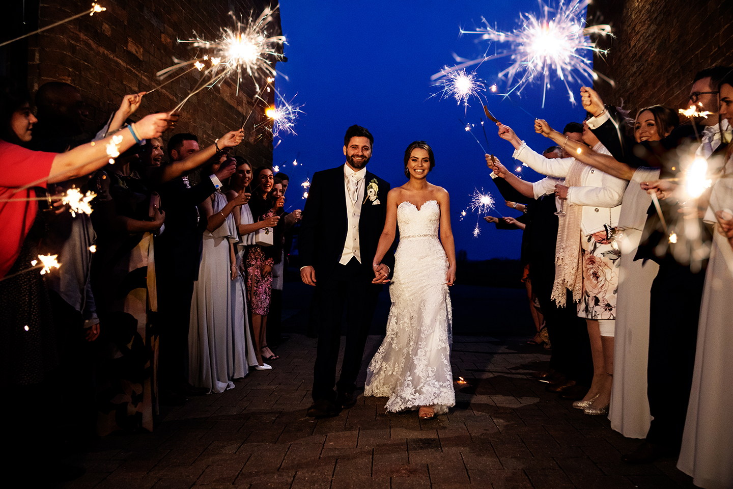 The bride and groom walk through a line of sparklers as their wedding day at Bassmead Manor Barns comes to an end