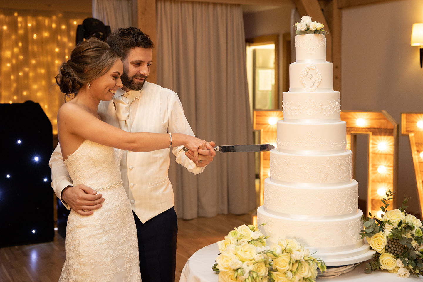 The newlyweds cut their wedding cake during their wedding reception at Bassmead Manor Barns