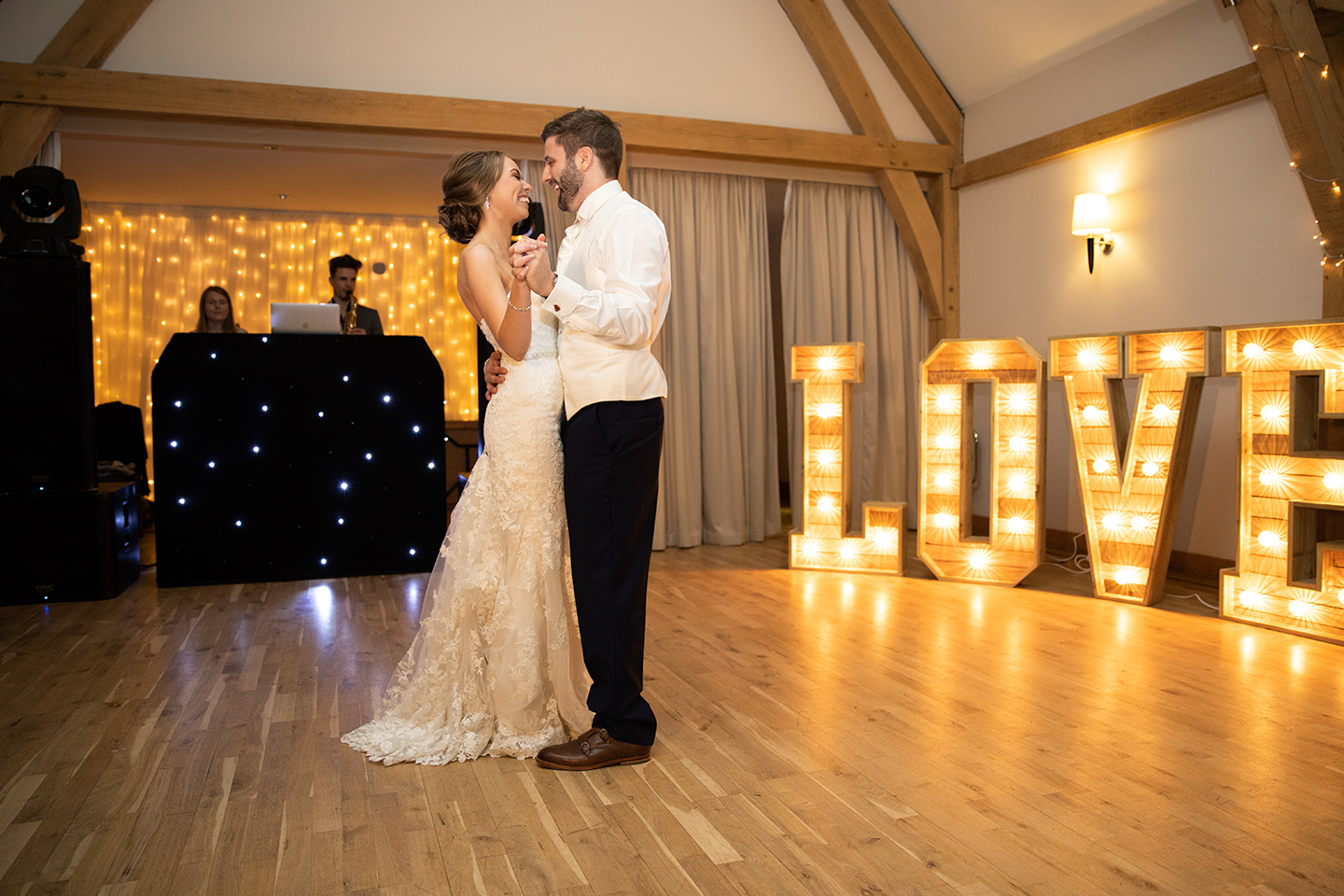 Newlyweds perform their first dance in the Bridge Barn at Bassmead Manor Barns during their evening wedding reception
