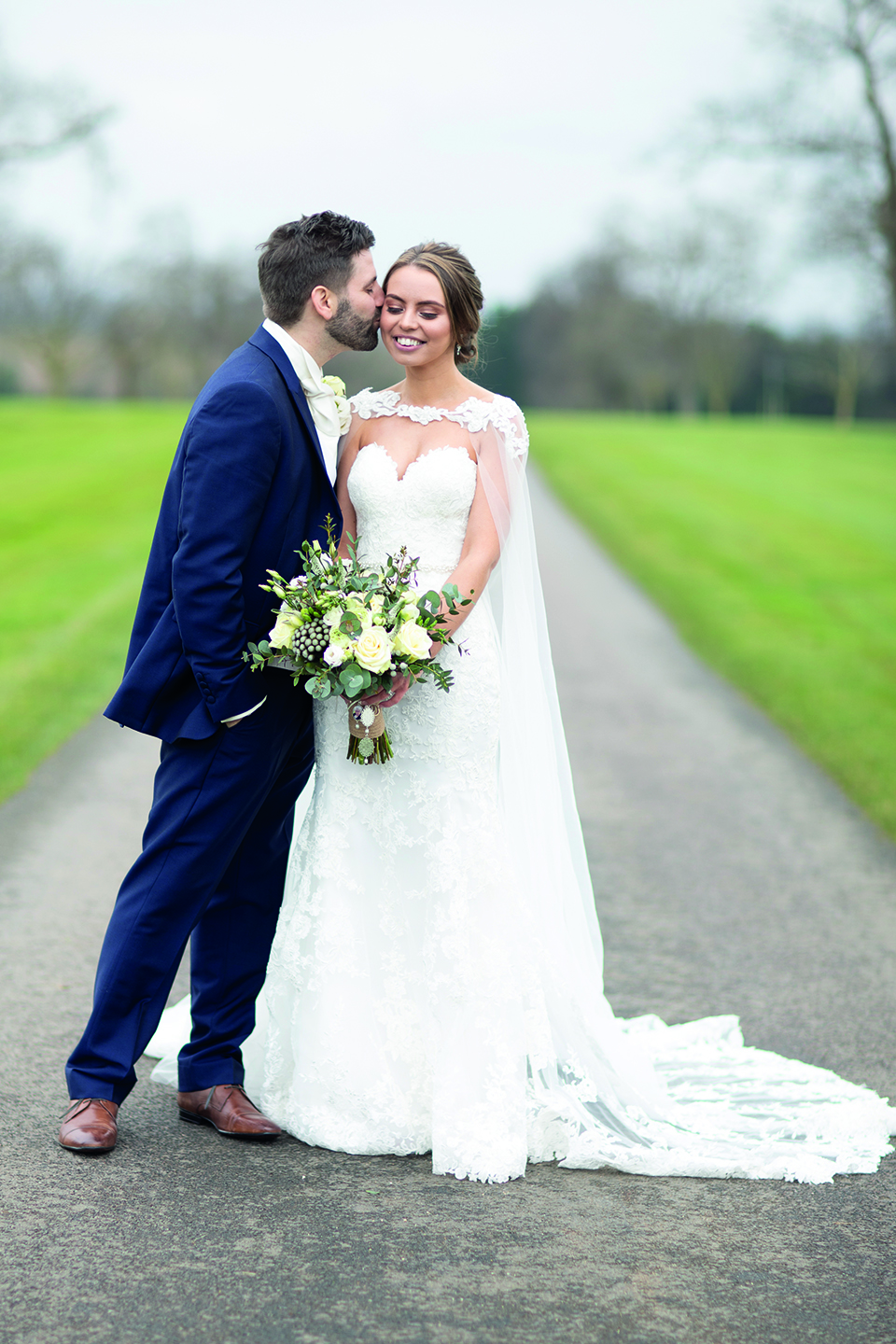 The bride holds a green and ivory wedding bouquet as the newlyweds enjoy a moment away from guests at Bassmead Manor Barns