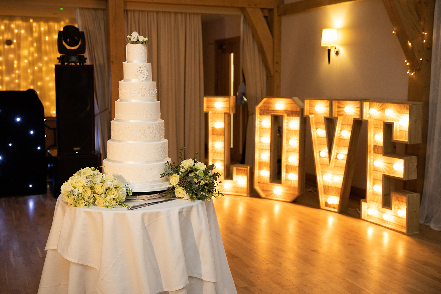 A wedding cake sits in front of large light up love letters in the Bridge Barn at Bassmead Manor Barns