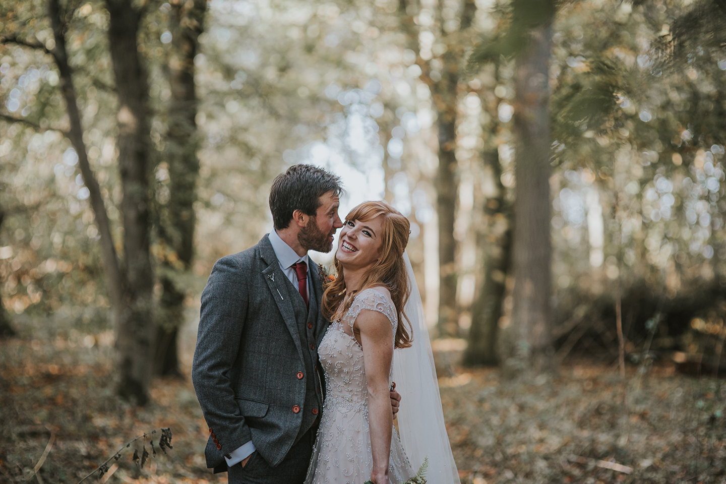 A bride and groom explore the woodlands at Bassmead Manor Barns wedding venue in Cambridgeshire