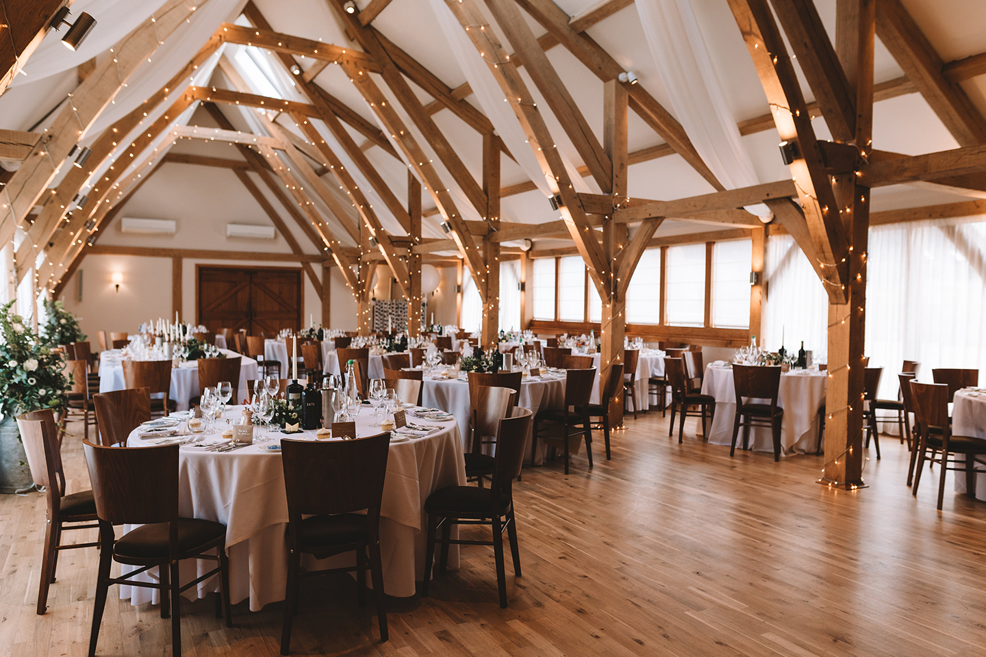 The light flooded Bridge Barn at Bassmead Manor Barns is set up for a wedding breakfast