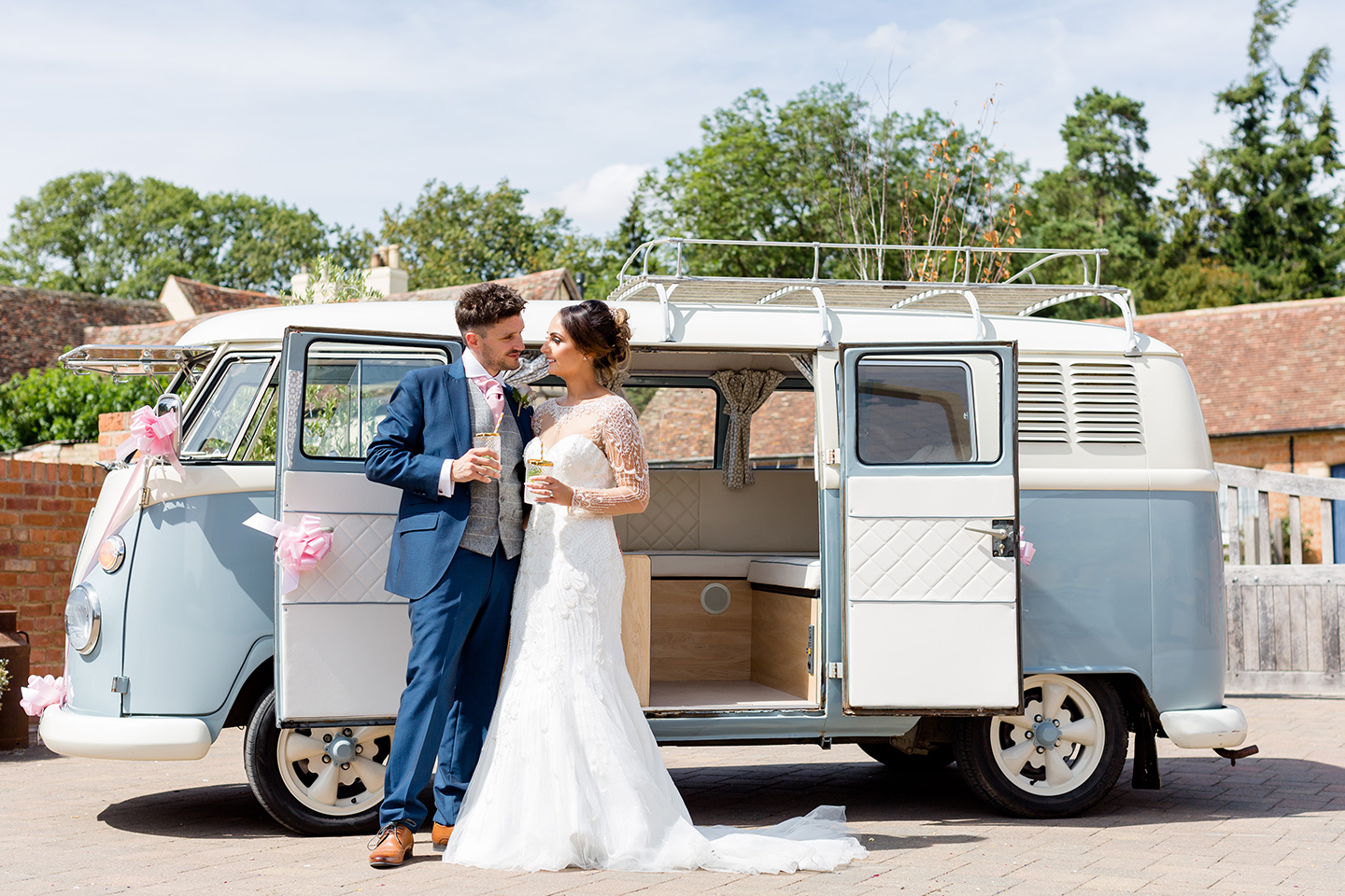 The newlyweds stand infront of a VW campervan wedding car after their summer wedding ceremony at Bassmead Manor Barns