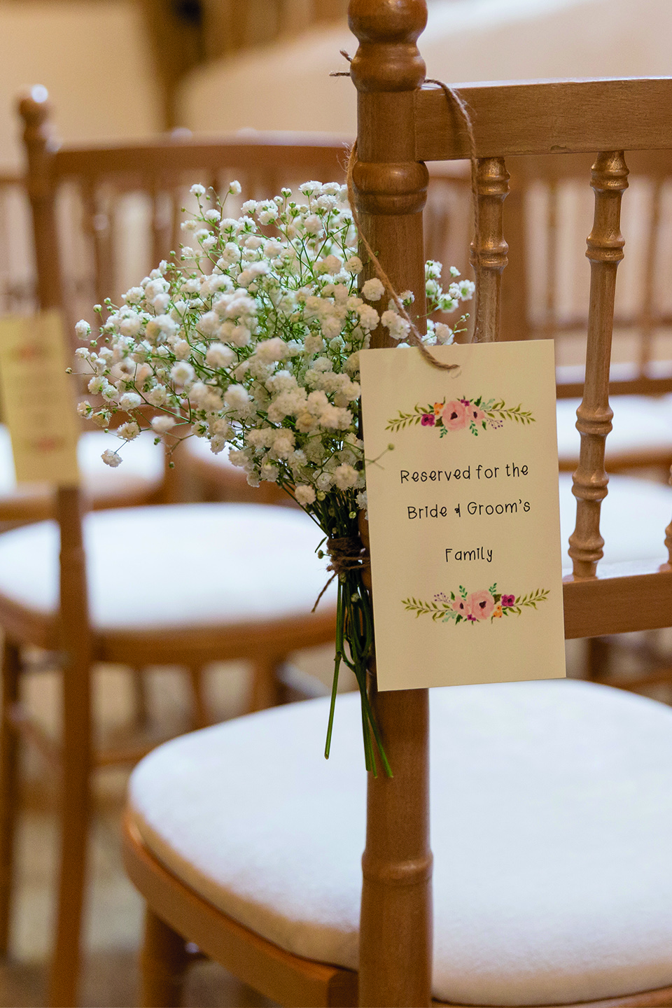 In the Rickety Barn at Bassmead Manor Barns chairs are decorated with floral posies and reserved seating tags