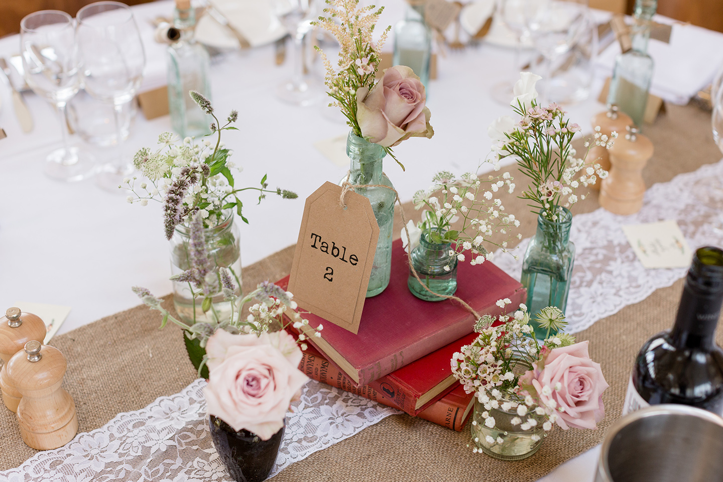 Books and jars of florals create rustic wedding table centrepieces for a summer wedding at Bassmead Manor Barns