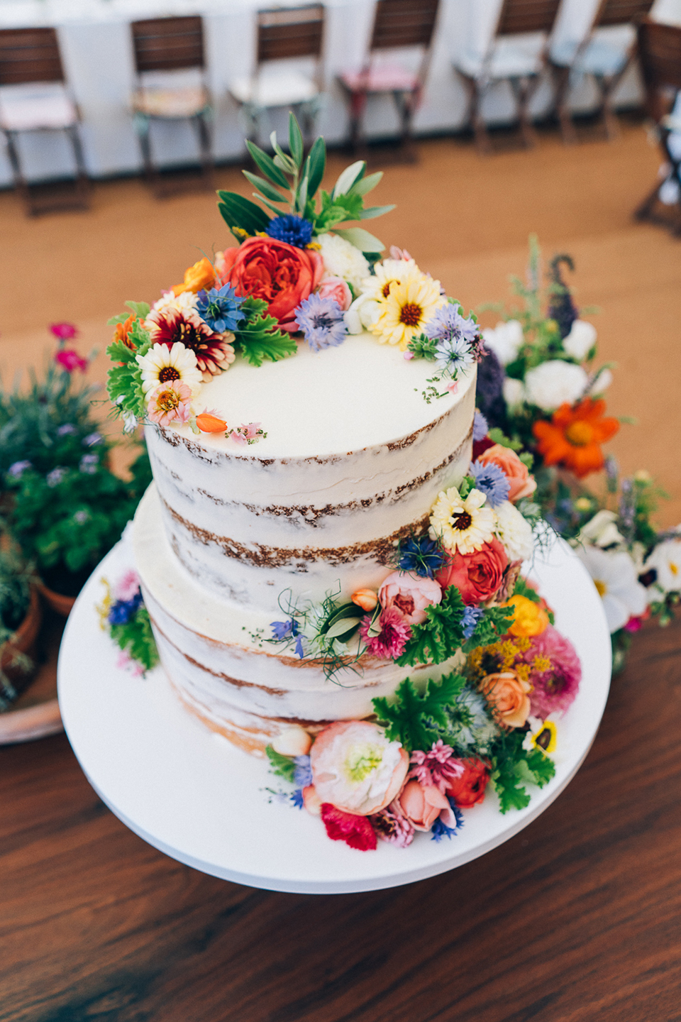 Bright flowers decorate a semi naked wedding cake that is ideal for a wedding at Bassmead Manor Barns