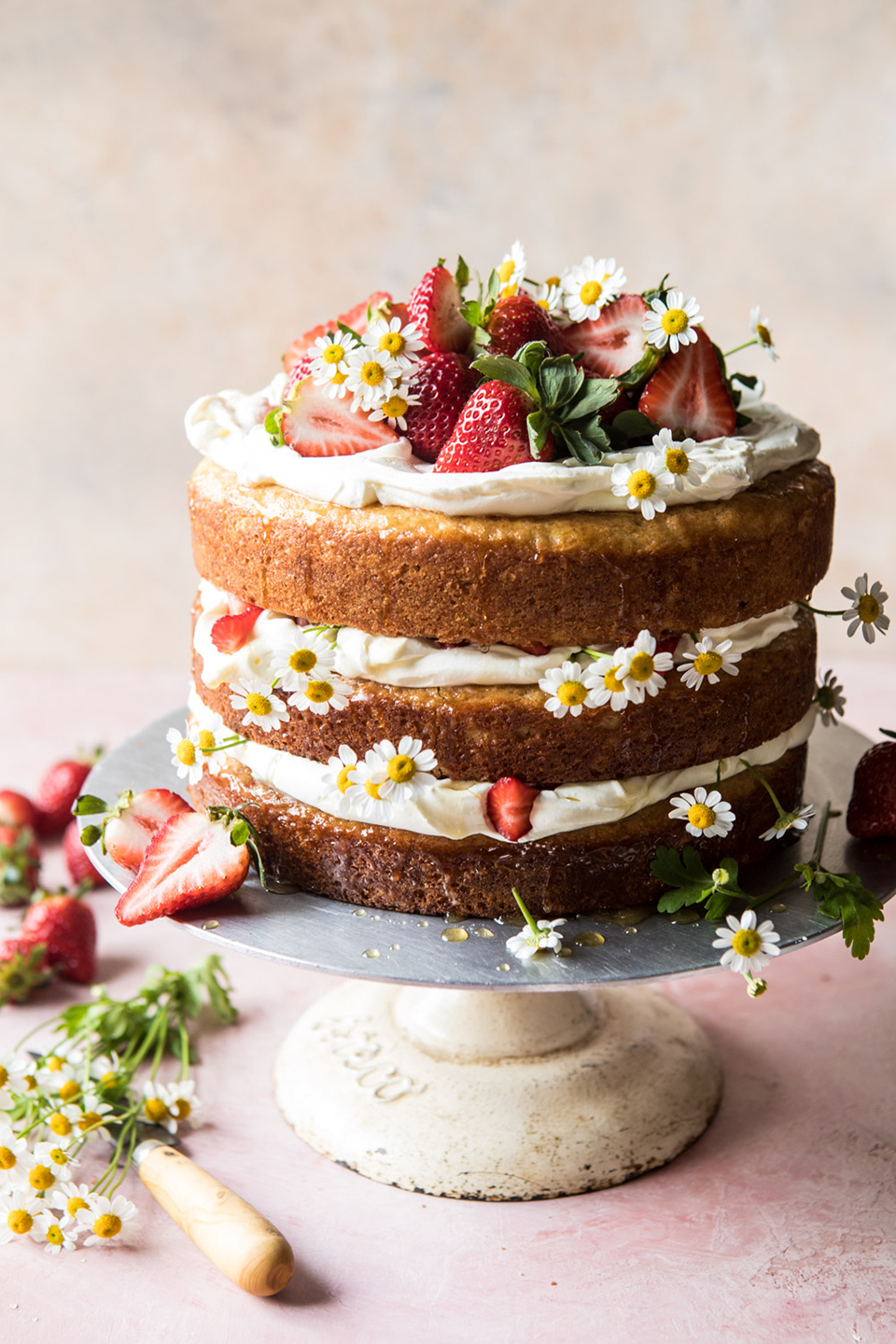 A naked cake decorated in fruit and flowers is ideal for a summer wedding at Bassmead Manor Barns