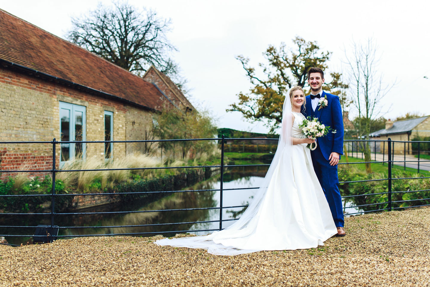The bride and groom stand by the pretty moat at Bassmead Manor Barns