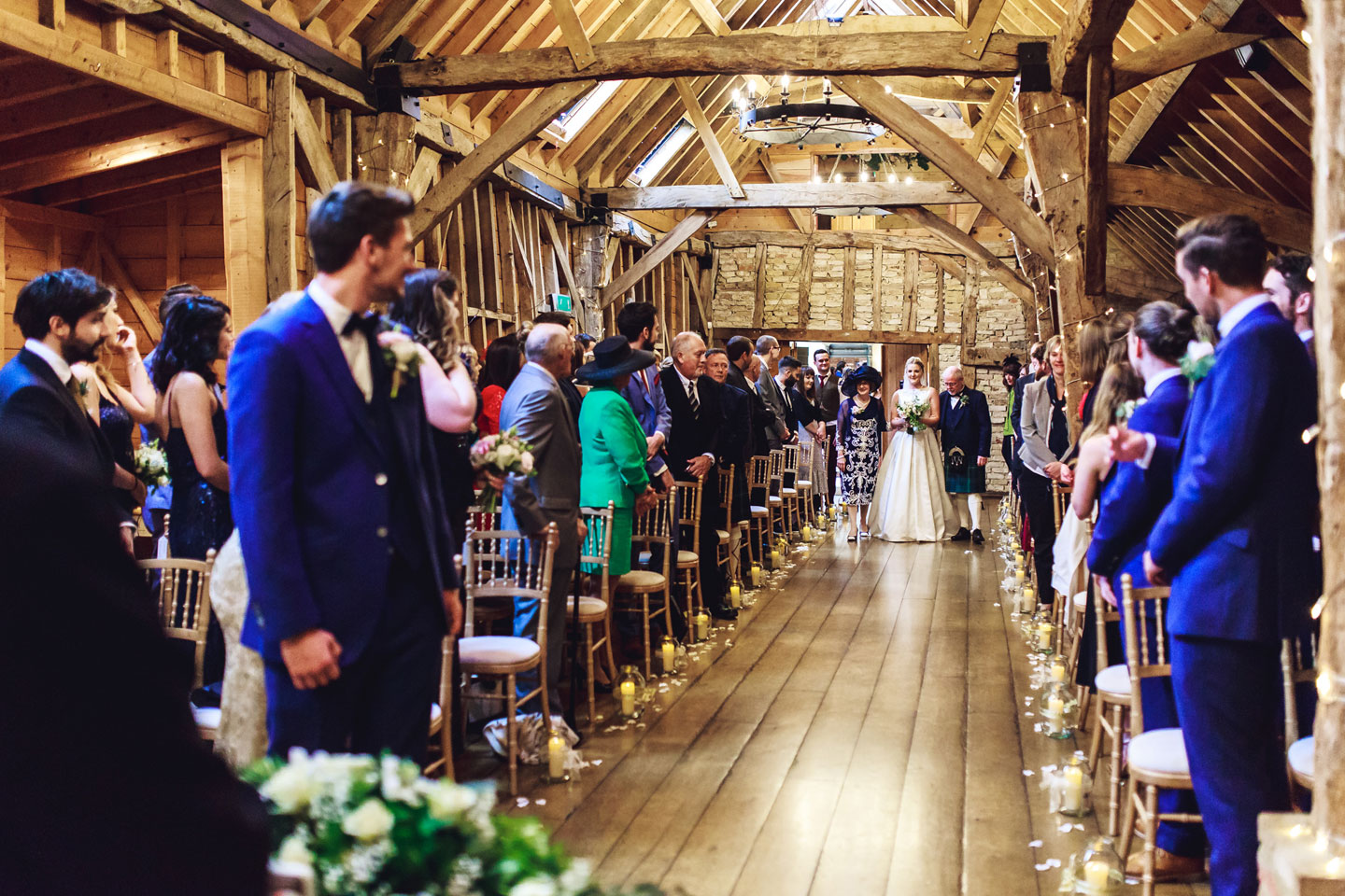 The beautiful bride walks down the aisle with her mother and father in the Rickety Barn