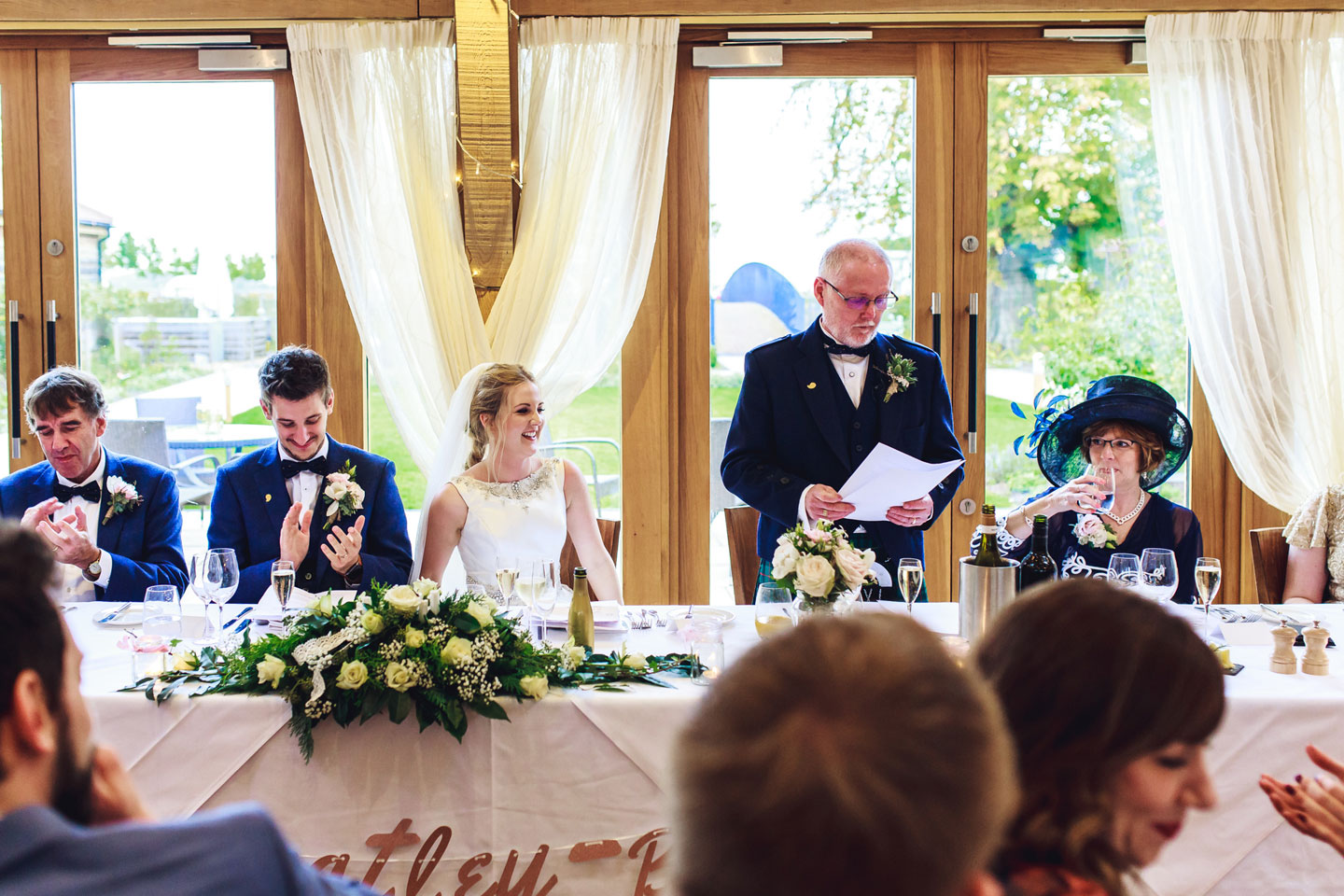 Guests look on as the father of the bride gets the wedding speeches under way