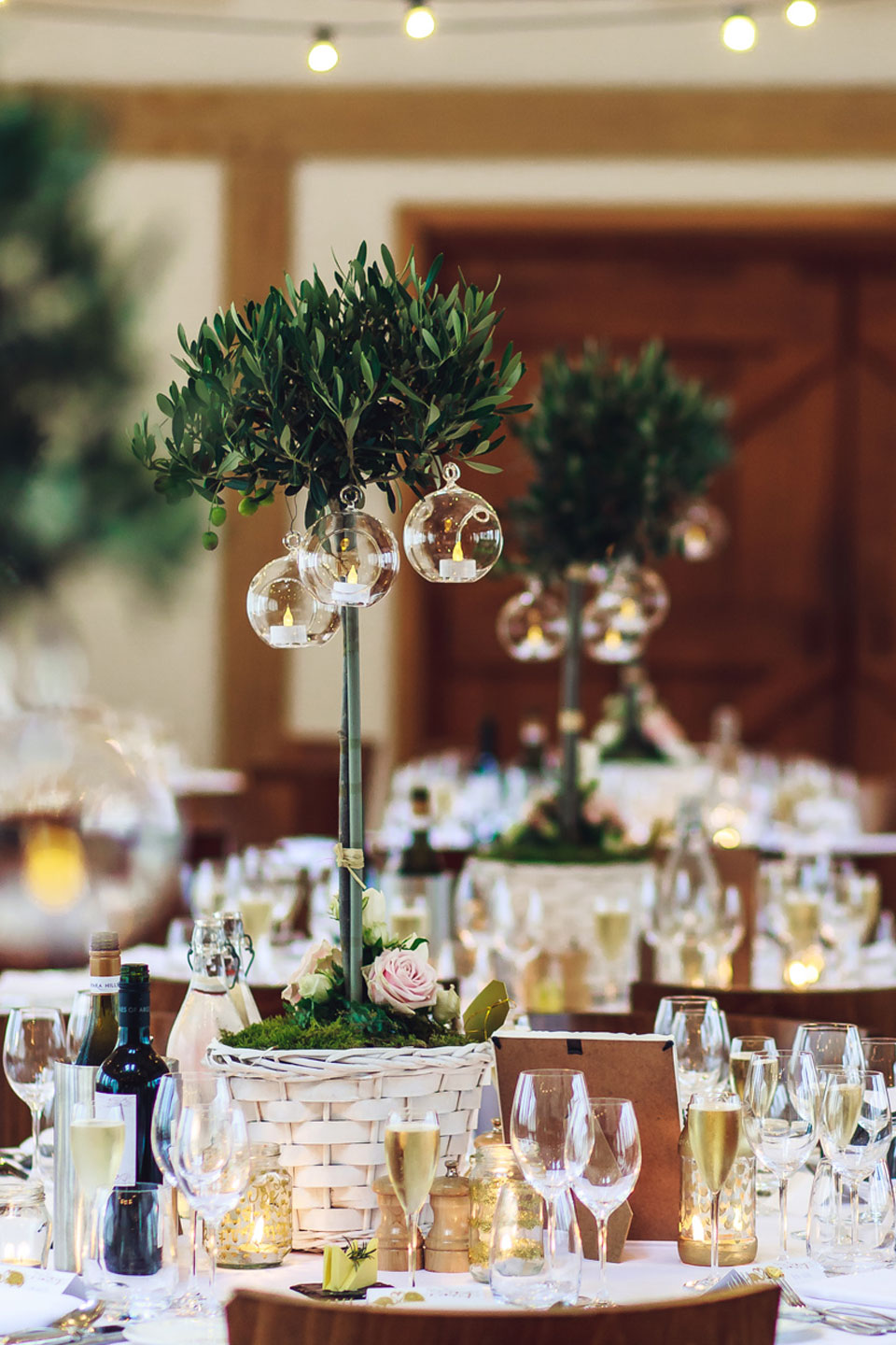 Glass circular candle holders hung from tall green plants for the wedding centrepieces