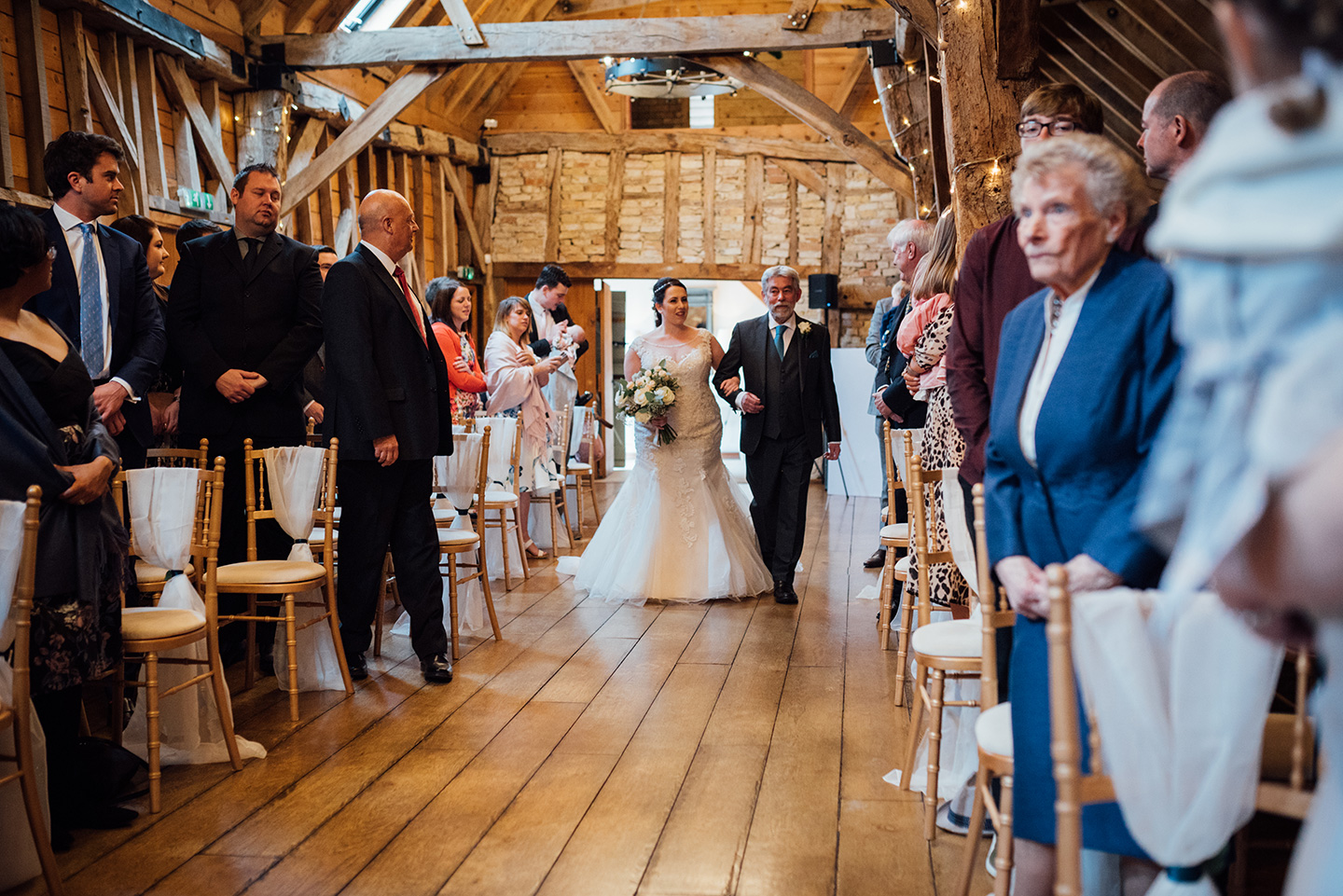 Bride makes her way down the aisle in the wedding ceremony barn
